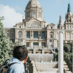 people near Museu Nacional d'Art de Catalunya in Barcelona under blue and white sky during daytime